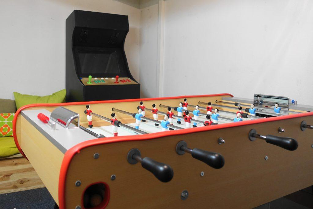 une salle de jeux avec borne d'arcade, babyfoot